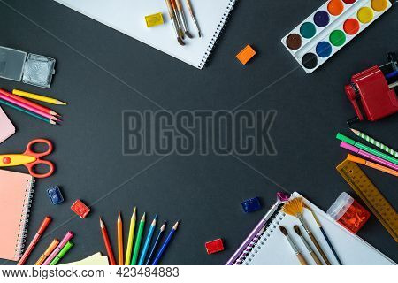 School Supplies Displayed On Blackboard Background. In Center, On Black Surface, There Is Space For