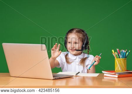 Smart Little Girl With Headphones Uses A Laptop To Study On The Internet, Welcomes A Distance Learni