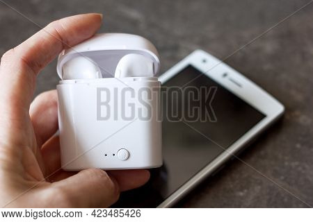Wireless White Headphones In A Container In The Inflow In Hand Against The Background Of A White Sma