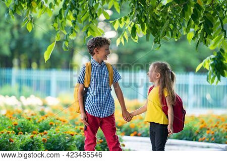 Primary School Pupil. Boy And Girl With Backpacks Walking Down Street. Happy Children Happy To Go Ba