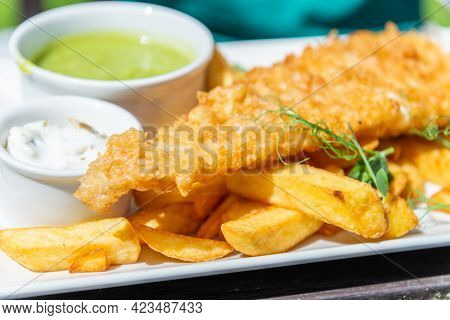 Traditional English Food Such As Fish And Chips With Green Mushy Peas Served In The Pub Or Restauran