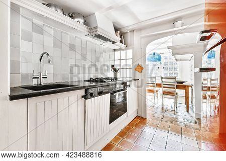 Well Organized Small Home Kitchen Interior With Sink Under Window And Light Furniture With Stove And