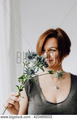 Cheerful woman holding a blue thistle