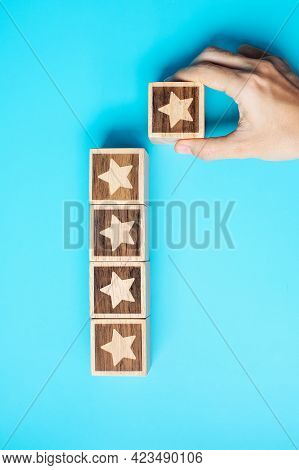 Hand Holding Star Block On Blue Background. Customer Choose Rating For User Reviews. Service Rating,