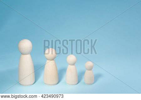 Wooden Figurines Standing In A Row From High To Low. Concept Person Growth On Blue Background. Manag