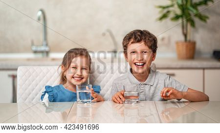 Funny Little Children Drink Water In The Kitchen At Home. The Boy And Girl Are Smiling Happily, Hold