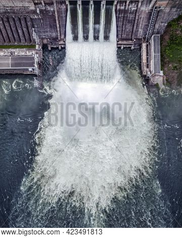 Water Discharge Stream Waterfall At The Hydroelectric Dam. An Overflowing Reservoir, A Huge Jet Of W