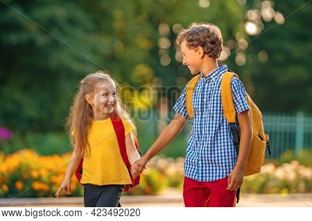 Primary School Pupils. Boy And Girl With Backpacks Walking Down Street. Happy Children Happy To Go B