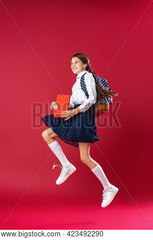 Mischievous Schoolgirl, In Uniform With Backpack And Books Jumps On Red Background. Dynamic Images.