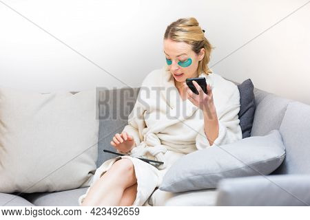 Young Female Entrepreneur Wearing Beauty Face Mask And Cosy Warm Bathrobe In The Morning, Working Re