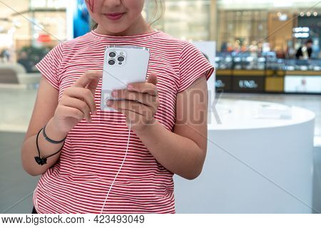 A Charming Little Girl Is Holding In Her Arms Apple Iphone 12 Pro Max Silver In The Apple Store. The