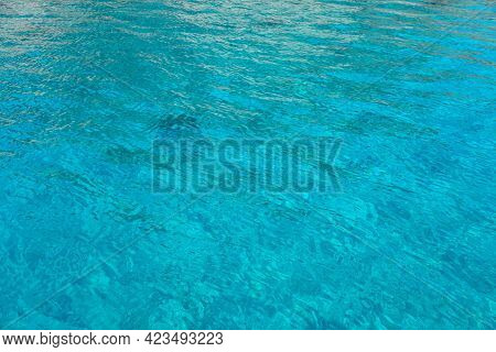 Sea Surface Turquoise Blue Color Background, Some Reflections. Calm Crystal Clear Water With Small R