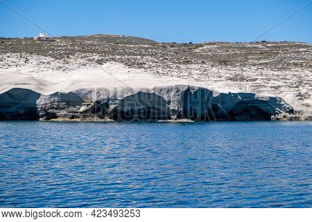 Sarakiniko Beach At Milos Island, Cyclades Greece. White Rock Formations, Cliffs And Caves Over Blue