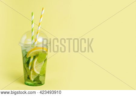 Mojito Cocktail In A Plastic Glass With A Tube On A Yellow Background. Ool Drink In The Summer For T
