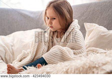 Sick Girl Is Sitting On The Sofa, Wrapped In A Blanket And Taking Her Temperature. An Unhealthy Sad