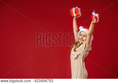 Merry Christmas! A Happy Little Girl In A Santa Hat Holds Up Her Hands With Gifts On A Red Backgroun