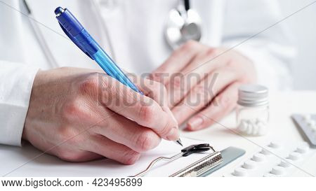 Close-up Of A Doctor Hands Writing A Prescription In A Medical Record On A Tablet. A Doctor In A Whi