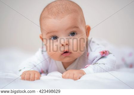 Cute Baby Lying On Bed On White Blanket And Smiling. Small Curious Child 4 Months, Caucasian, Lies O