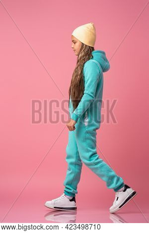 Teen Girl In Beanie, Turquoise Warm Jumpsuit With Hood In Sneakers Go On Pink Background Studio. Ful