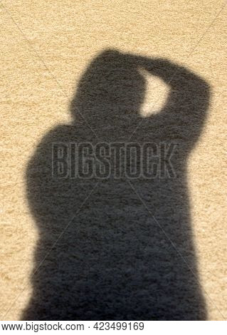 A Strange Posture Of An Unidentified Person In Shadow Form Against A Tan Colored Grainy Background.