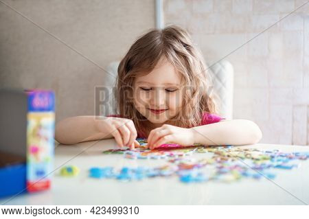 Little Girl With Light Wavy Hair Collects A Puzzle At Home And Has Fun. The Child Collects A Picture