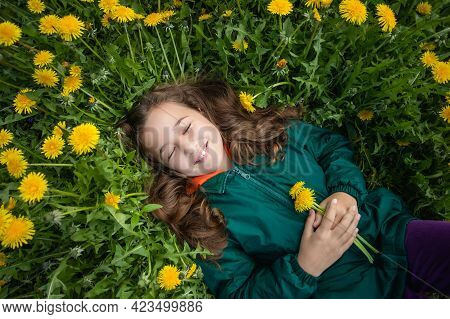 Close-up Of Happy Little Russian Girl With Her Hair Loose And With Smile, With Bouquet Of Dandelions