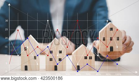Man Hand Choosing Mini Wood House Model From The Model On Wood Table, Planning Buy Real Estate, Plan