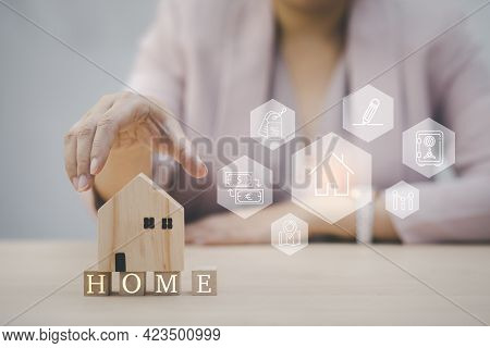 Home Insurance And Security Ideas Concept, Woman Hand Touch Wooden Home And Icon Of Property Value D