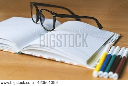 On The Table Is An Office Notebook, Glasses, Markers. Office Supplies. Black-rimmed Glasses, Colored