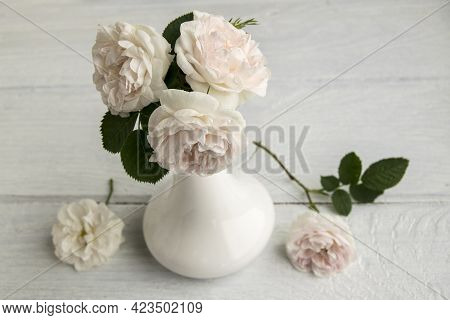 Delicate Pink Roses Are In A White Vase. The Bouquet Consists Of Three Flowers. The Vase Is On A Woo