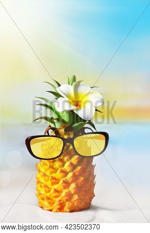 Pineapple With Flower And Sunglasses In The Beach. Summer Concept.