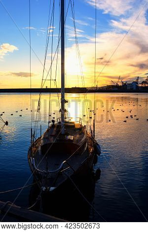 Beautiful Sunset And Silhouette Of A Boat In The Port Of Burgas, Bulgaria.