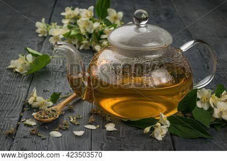 A Glass Teapot Of Jasmine Tea On A Black Wooden Table. An Invigorating Drink That Is Good For Your H