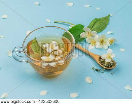 Jasmine Flowers And Jasmine Tea On A Blue Background. An Invigorating Drink That Is Good For Your He