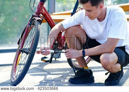 Pumping Air Into An Empty Bicycle Wheel. A Man Shakes A Bicycle Wheel In A Park. A Person Inflates A