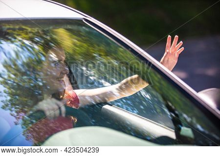 Motion Blured Image Of Happy Young Woman Driving A Car On A Summer Road Trip Travel Vacations. Shot