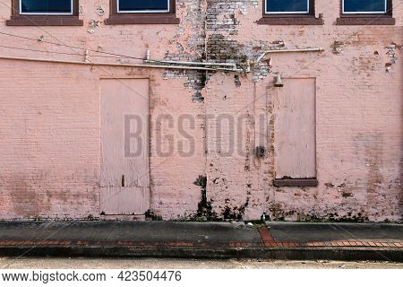 A Rundown Deserted Alley Building With Boarded Up Doors And Windows Painted With Faded Pink Paint.