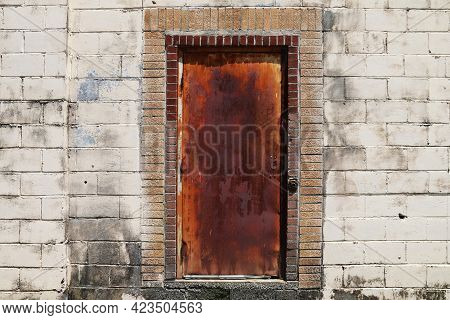 A Rusty Red Old Metal Steel Door In A Back Alley Concrete Block Abandoned Warehouse Building.