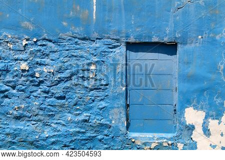 A Weathered Faded Blue Painted Stone Building Wall Facade With Concrete Cinder Blocks Window Doorway