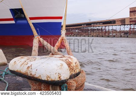 At The Mooring Bit Moored A Large Ship, Tied With Large Ropes