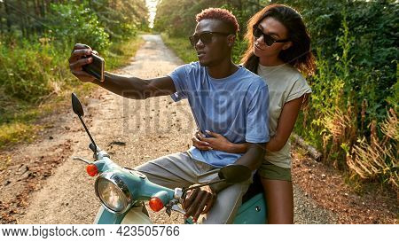 Cheerful African American Young Friends Taking Selfie While Riding Scooter In Sunny Summer Nature, W