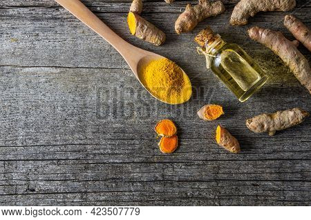 Glass Bottle Of Turmeric Essential Oil With Turmeric Roots On Wooden Background ( Curcuma Longa )