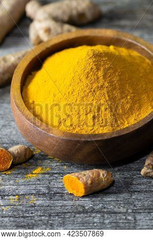Turmeric Powder In Spoon Or Bowl And Fresh Turmeric Root On Wooden Background, Spice Concept, ( Curc