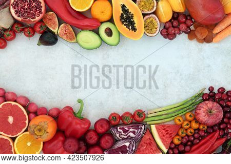 Plant based immune boosting vegan health food high in lycopene with fruit and vegetables also high in antioxidants, anthocyanins, vitamins, minerals,  and fibre. Border on mottled background.