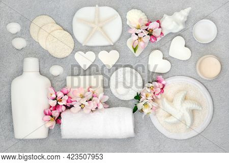 Natural skincare cleansing ingredients and products with soaps, scrubs, sponges, moisturising cream and apple blossom flowers with decorative seashells. Flat lay on mottled grey background.