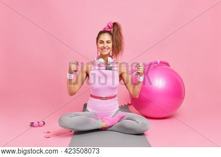 Happy Fitness Female Model Sits Crossed Legs On Mat Stretches Expander Trains Muscles Dressed In Bod