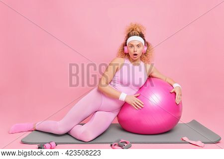 Stunned Slim Woman Practices Yoga At Home Leans At Fitness Ball Wears Sportswear Headband Poses On F