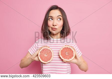 Half Length Shot Of Thoughtful Millennial Girl With Eastern Appearace Holds Two Halves Of Fresh Grap