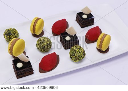 French Pastries In A Platter As Petit Four With Macaroons, Chocolate Cake, Pistachio Balls Etc.