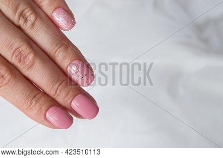 Beautiful Soft Pink Varnish And Sparkles On Nails - Gel Varnish Salon Coating Manicure.